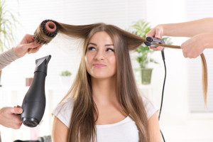 Hairdressers straightening long brown hair with hair dryer and round brush and hair irons.